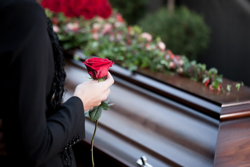Woman holding rose at funeral