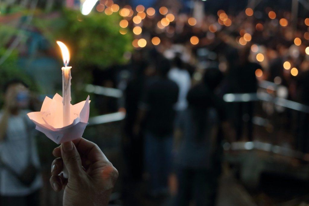 Holding candle at funeral