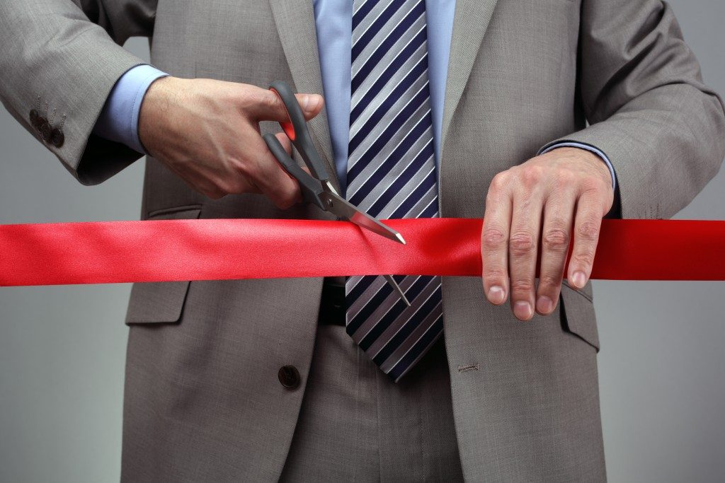 Man cutting a ribbon for the opening of a new business