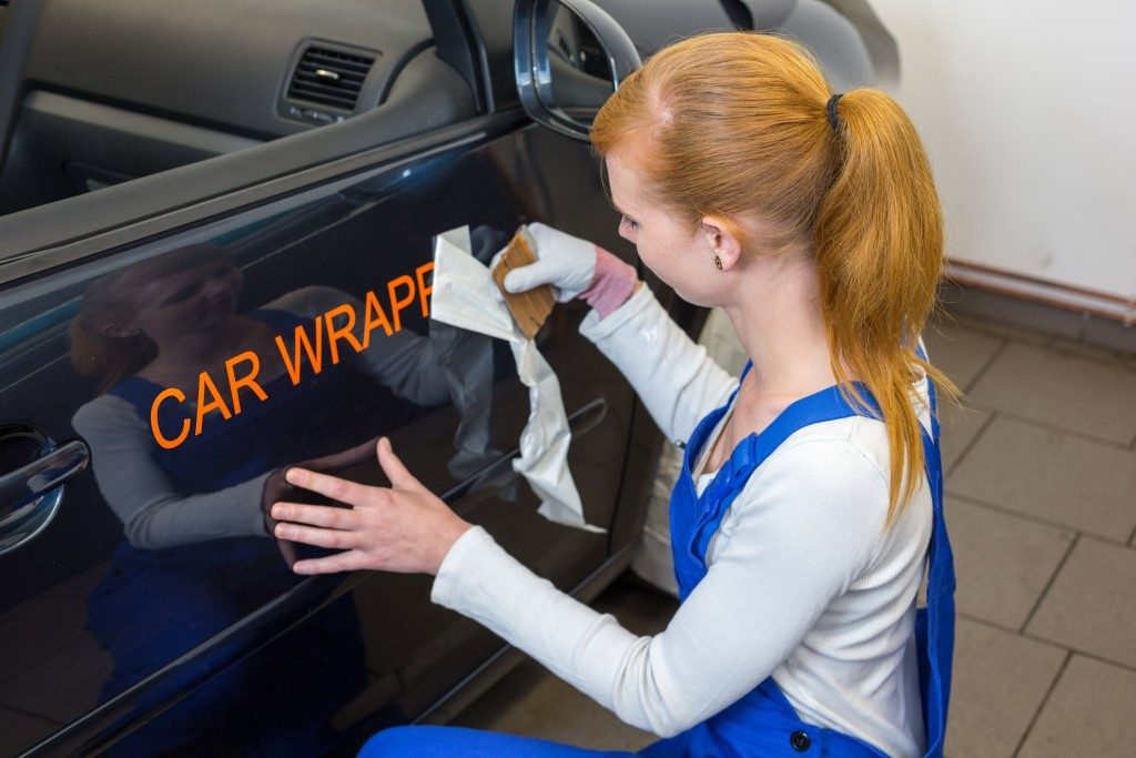 Car branding specialist puts logo with car wrapping foil