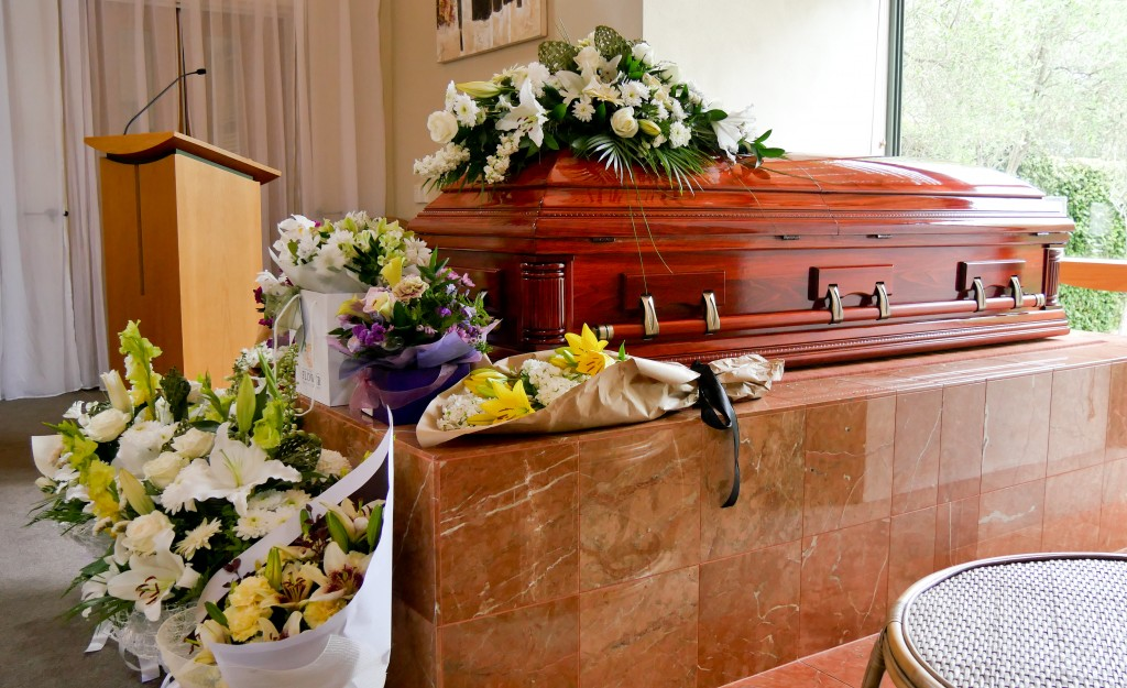 Casket surrounded with different types of flowers