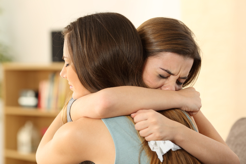Woman crying while hugging