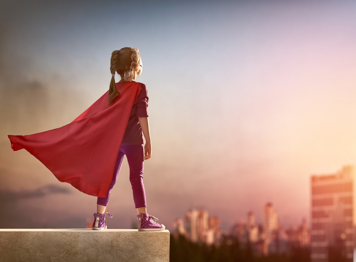 Little girl wearing a red cape being a superhero in her imagination