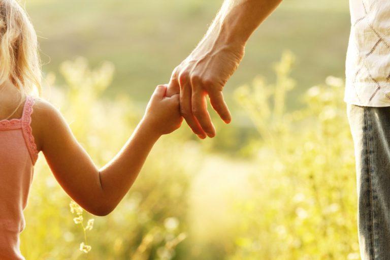 Little girl holding her dad's finger