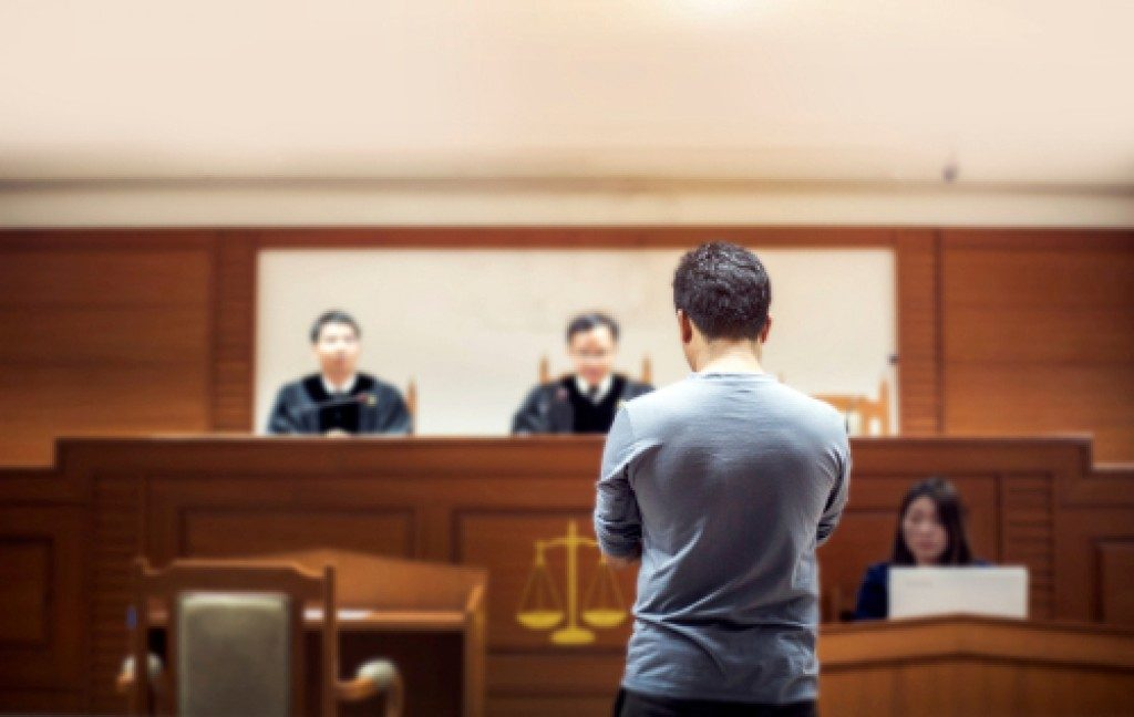 man in front of judges at court room