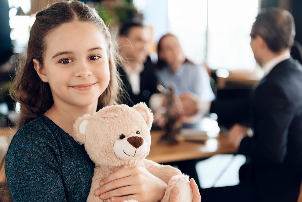 Little girl holding a teddy bear with parents in the background