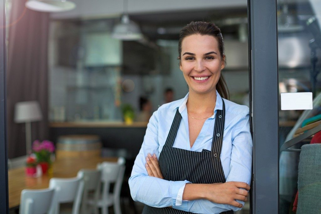 smiling entrepreneur standing at the side of the front door of her restaurant