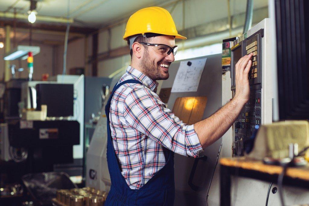 machine operator checking and doing maintenance