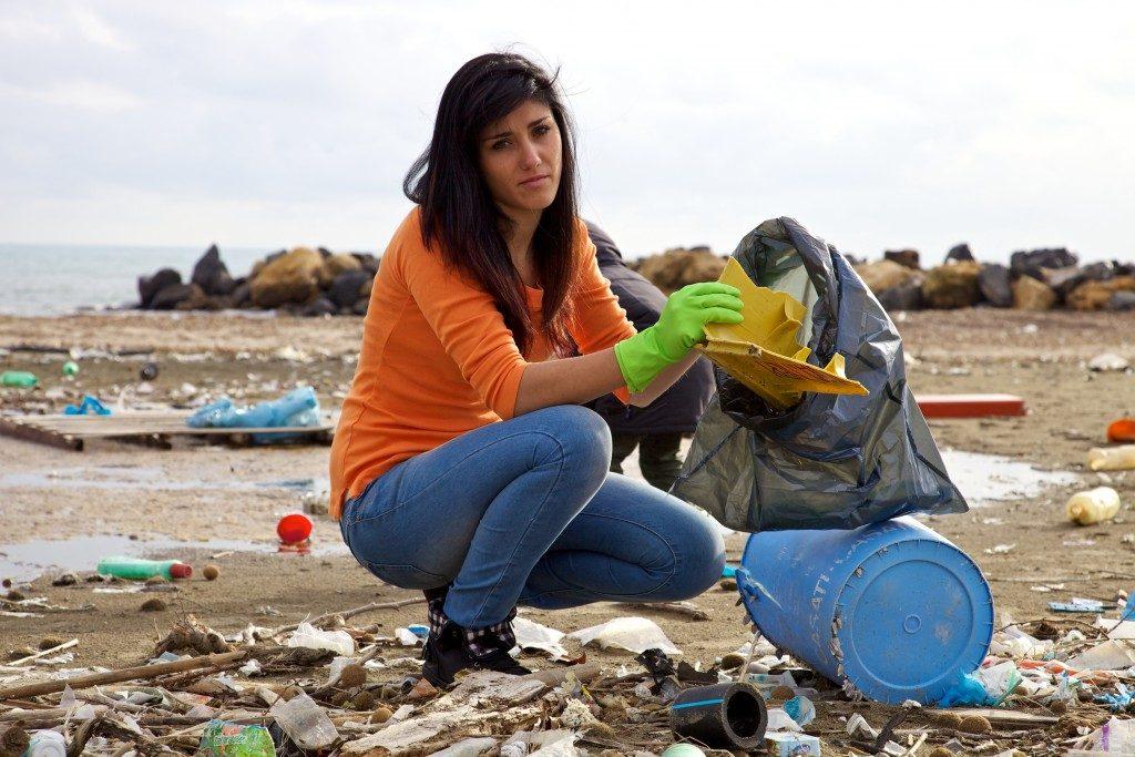 Sad woman picking up dump on dirty beach