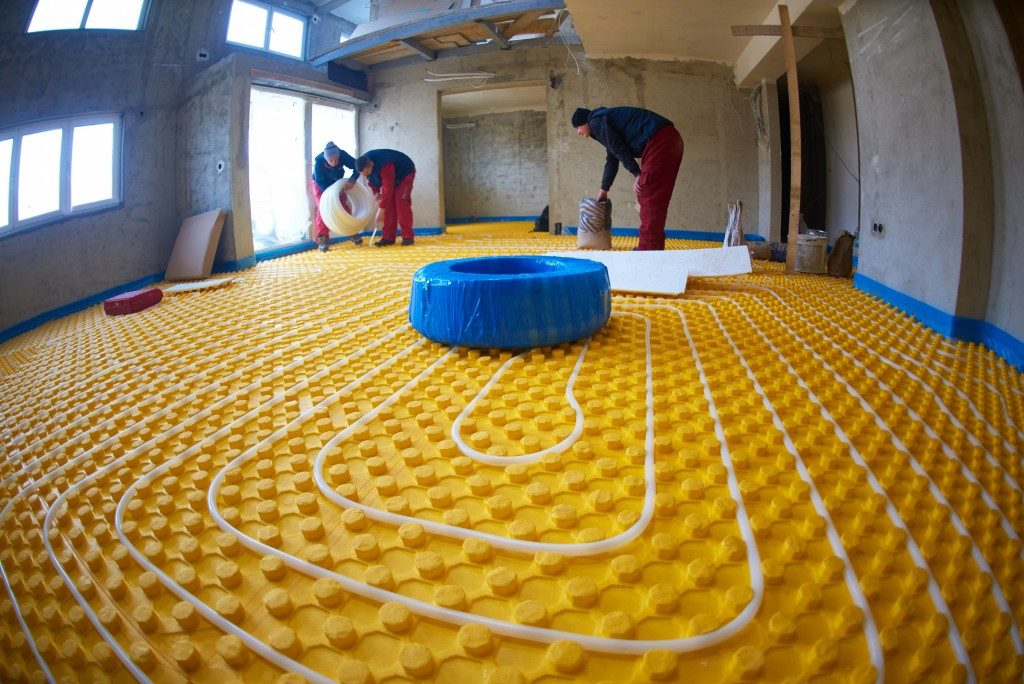 group of workers installing underfloor heating