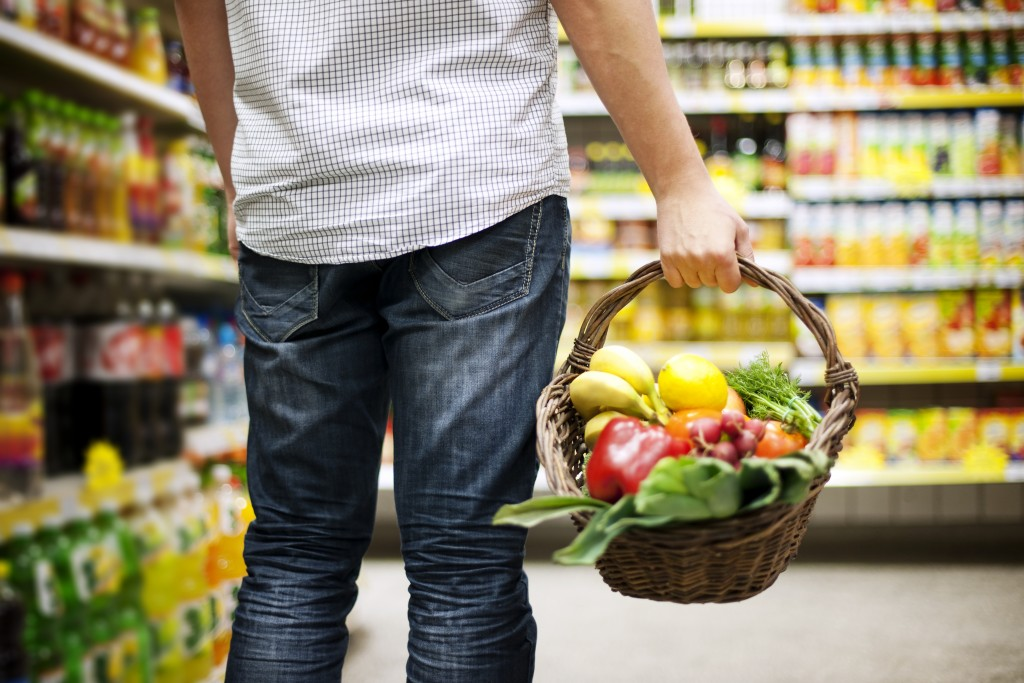 man holding a basket full of vegetables and fruits in the supermarket