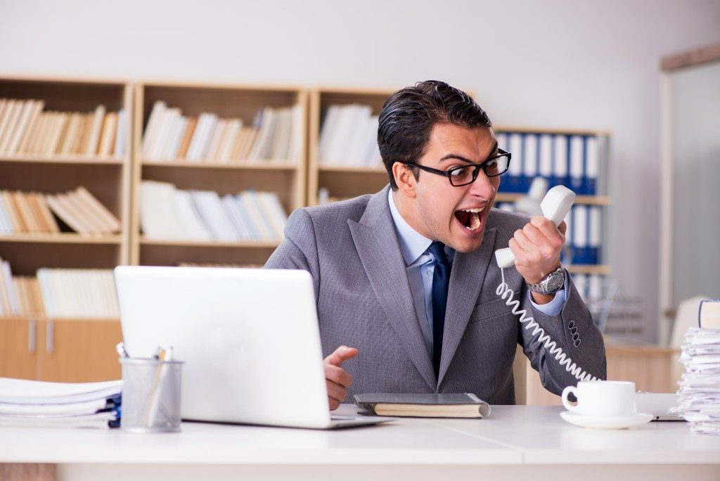 man screaming on the phone at work