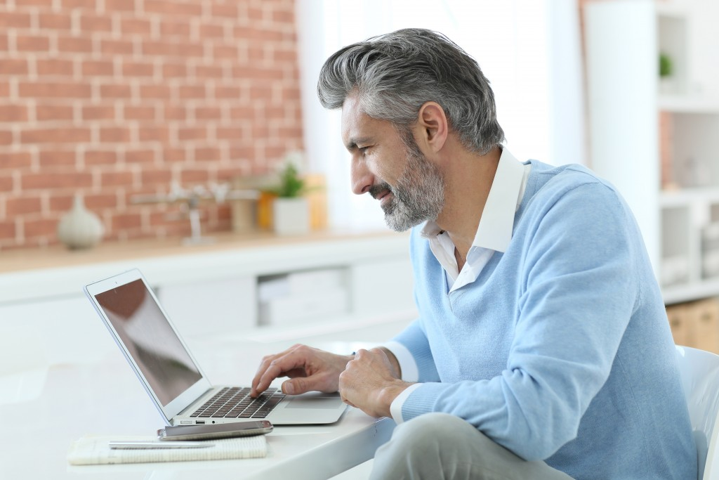 mature man working from home with laptop