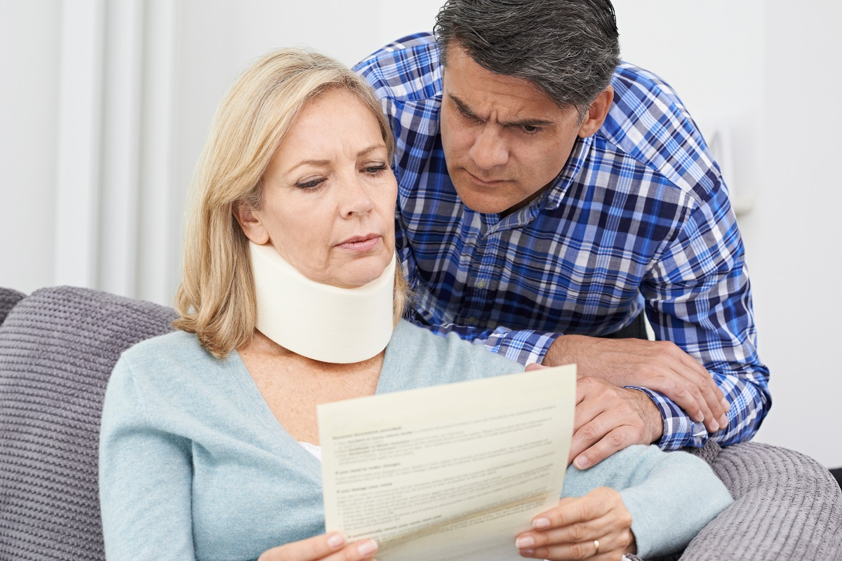 Woman with neck brace and mam reading a document