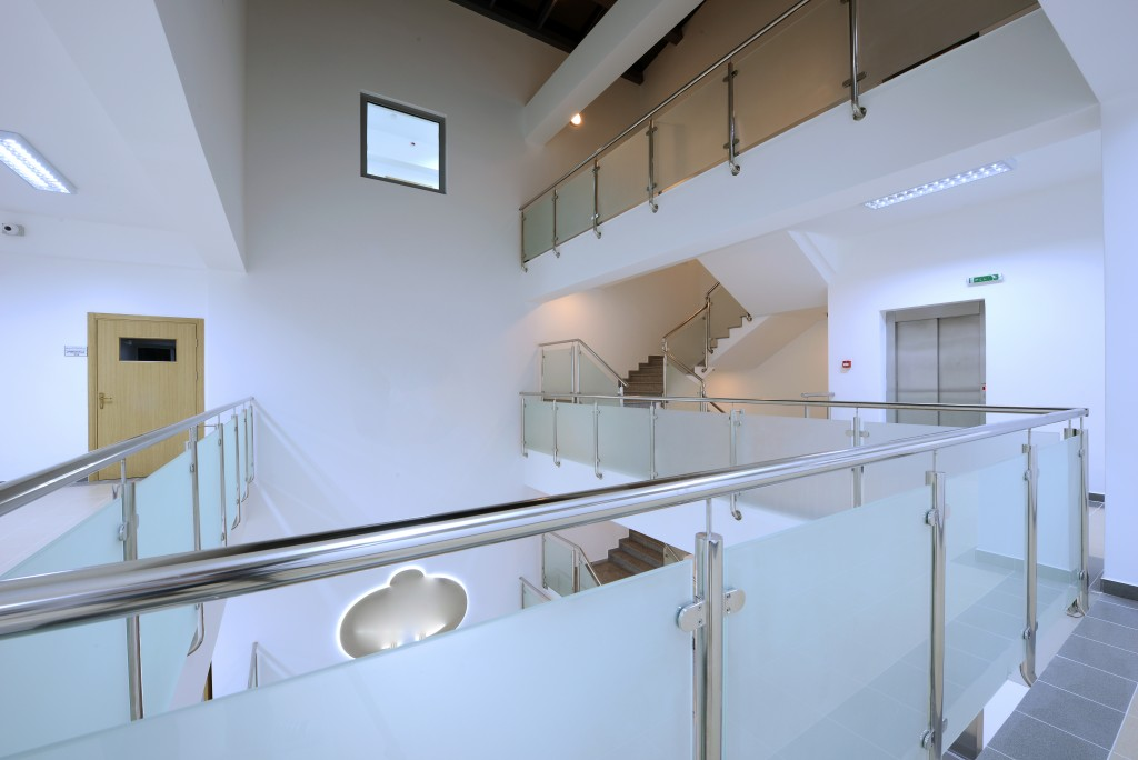Modern staircase and hall with glass banister in a office building