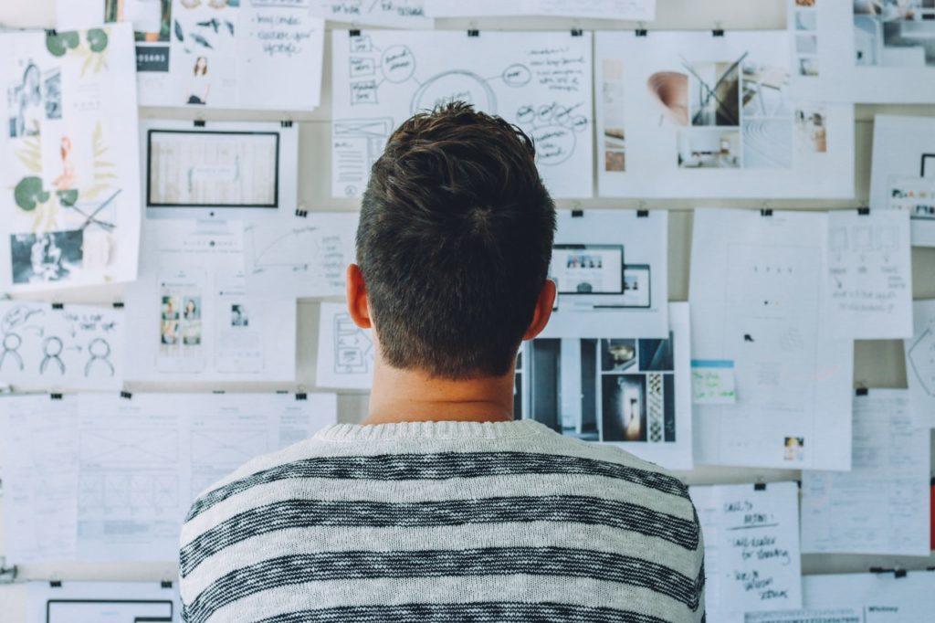 man looking at illustrations
